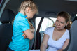 Resentful child refusing get safety car seat under mother look