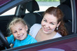 Mother with young daughter sitting together on driver car seat