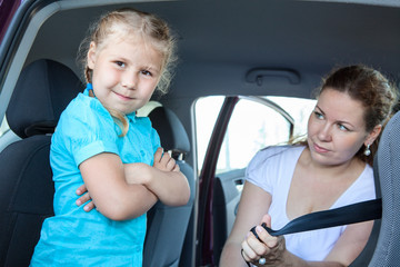 Resentful child ignoring mother forcing to seat in safety car
