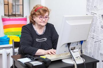 Senior woman typing keyboard button on computer