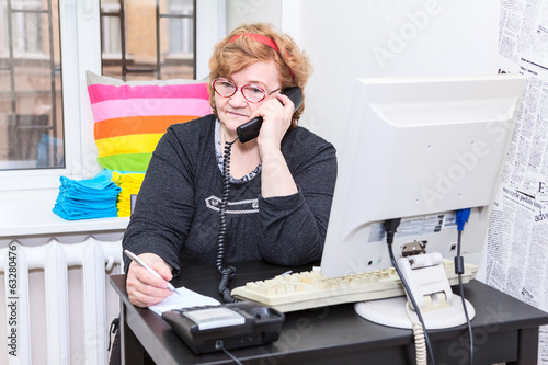 Senior Caucasian woman calling on telephone in office