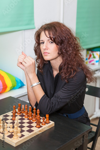 Thoughtful girl sitting at the board with chess