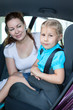 Mother with little daughter sitting on back seat of car