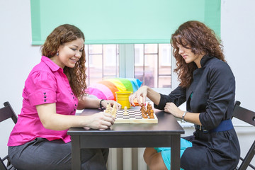 Two young women playing chess