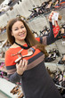 Attractive smiling woman choosing shoes in shopping center