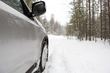 Offroad car standing on snowy forest road, copyspace