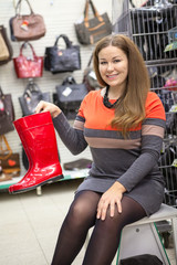 Smiling young woman showing red waterboots