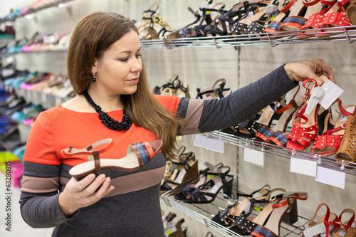 Beautiful Caucasian woman choosing shoes in shopping center