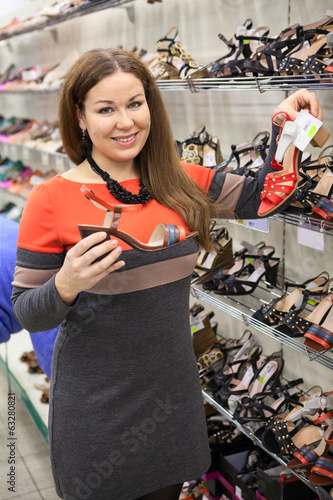 Attractive woman buying shoes in shopping center