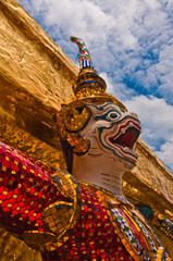 Ancient Thai sacred giants in front of the golden pagoda at the