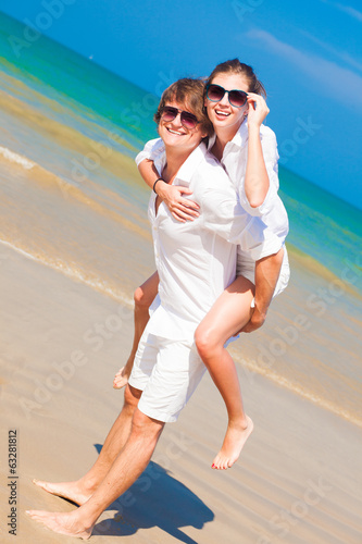 Happy couple in sunglasses and white clothes on holiday