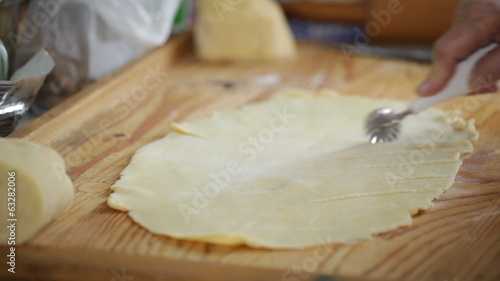 Closeup of senior female hand cutting pastry for apple strudel.