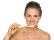 Portrait of smiling young woman brushing teeth