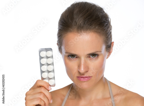 Portrait of serious woman showing blistering package of pills