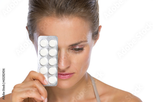 Portrait of serious young woman with blistering package of pills