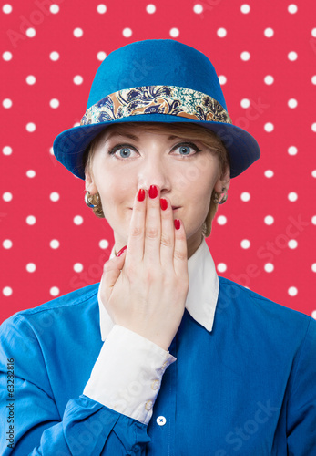 Woman in a blue hat hiding a smile, red polka dot background