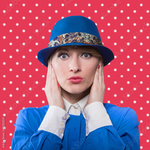 Woman with hands holding her face, red polka dot background