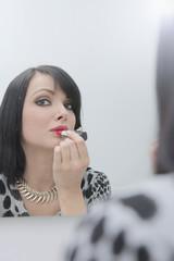 Attraktive Frau beim schminken im Spiegel