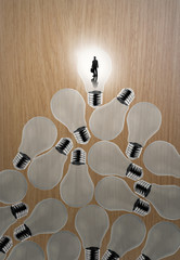 businessman standing at 3d growing light bulb standing out from