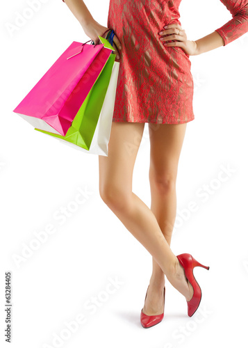 close up view on beautiful female legs and hands with paperbags