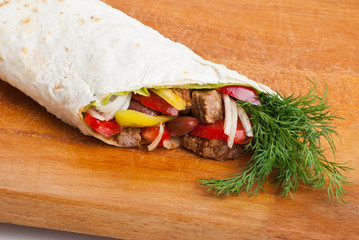 beef burrito with peppers, onion and tomato