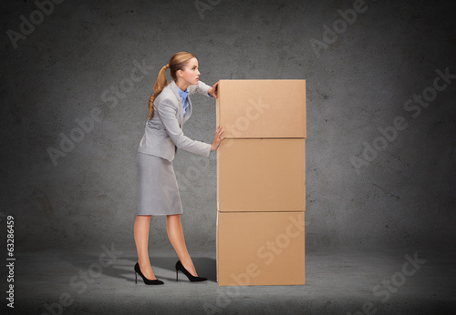 busy businesswoman pushing tower of cardboards