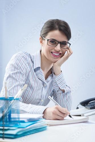Cute businesswoman smiling at desk