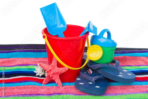 beach toys with flip flops and starfish on towel