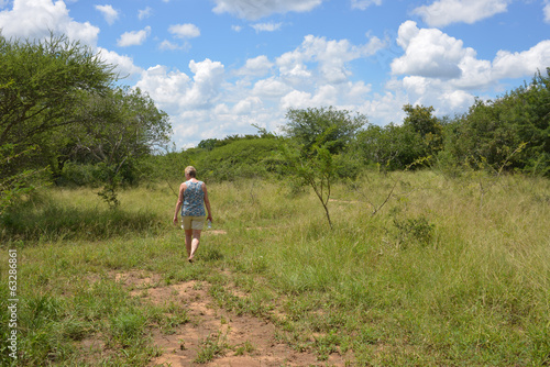 woman walking in nature with bleu sky and white clouds in africa