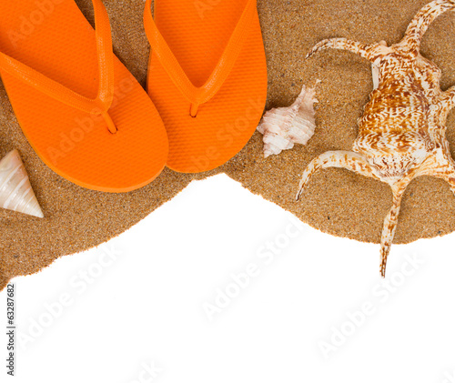 orange sandals and shells on sand