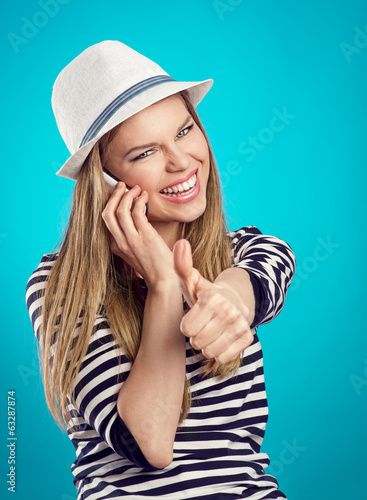 Happy toothy woman with phone showing thumb up