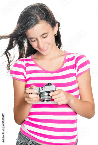 Pretty young girl looking at images on a compact camera