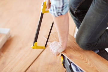 close up of male hands cutting parquet floor board