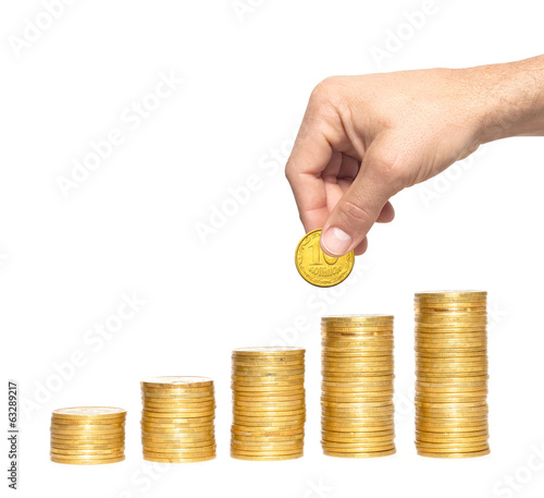 Savings, increasing columns of gold coins and man hand