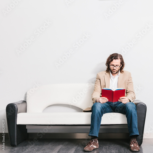 Young Man Reading a Book in a Waiting Room