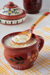 Spoon of milk soup with noodles and cup