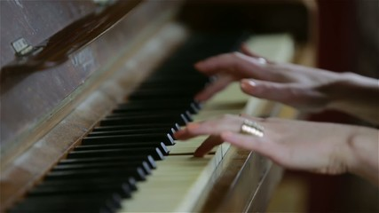 Female hands playing the piano (close-up)