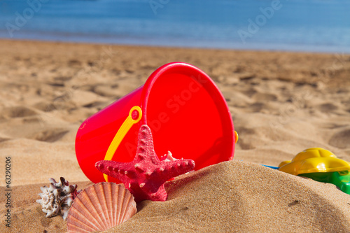 bucket with seshells in sand on sea shore