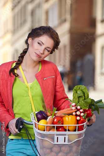 Pretty young woman with bicycle and groceries in old town street
