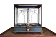 Antique balance scale in wood cabinet with white background.
