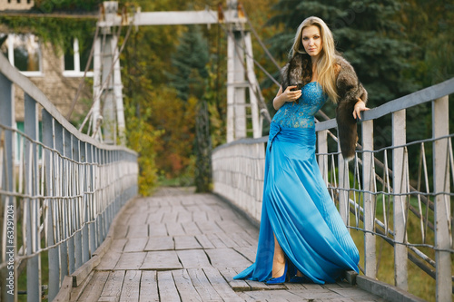 Beautiful blond woman in blue dress standing at the metal gate