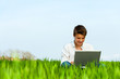 Boy in green field with laptop.