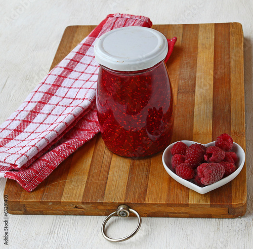 Raspberry on a background of jars of jam