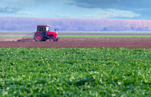 Red tractor working on thre agricultural field