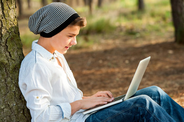 Teen boy socialising on laptop outdoors.