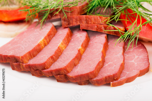 Sliced meat on the plate close up