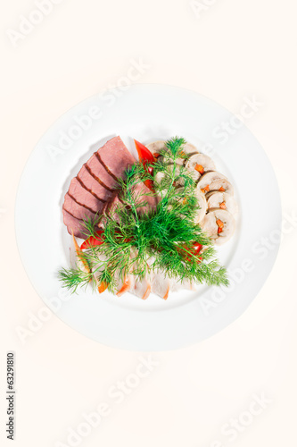 Sliced meat on the plate with dill and sliced pepper