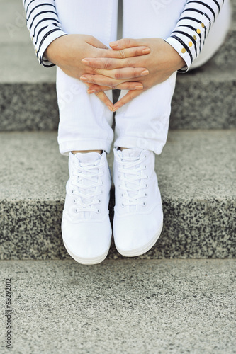 White sneakers on girl legs - closeup