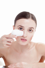 Woman with brush for deep cleansing facial. Skin care concept.