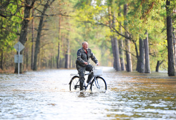 the man by bicycle goes on the flooded road